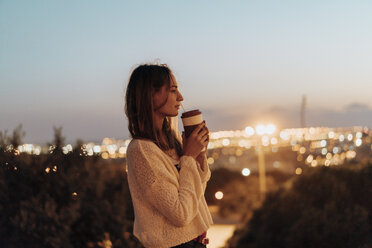 Spain, Barcelona, Montjuic, young woman holding takeaway drink at dusk with city lights in background - AFVF01988
