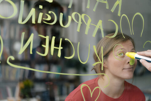 Portrait of young woman behind windowpane in a cafe with hand writing - KNSF05292