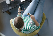 Overhead view of young woman with cell phone and espresso in a cafe - KNSF05298