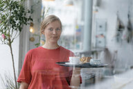 Portrait of young woman serving coffee and cake in a cafe - KNSF05304
