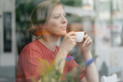 Young woman with cup of coffee behind windowpane in a cafe - KNSF05310
