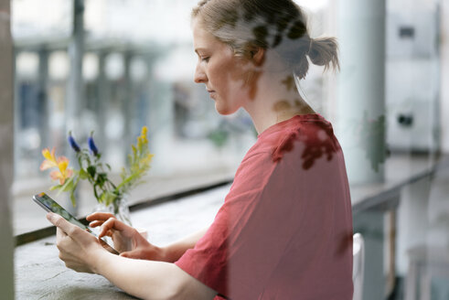 Young woman using tablet at the window in a cafe - KNSF05313