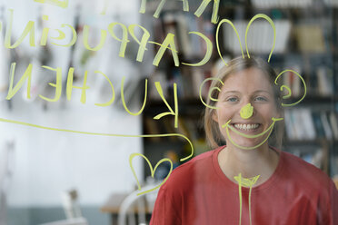 Portrait of happy young woman behind windowpane in a cafe - KNSF05319