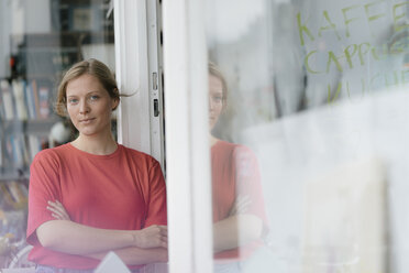 Portrait of confident young woman at French door in a cafe - KNSF05322