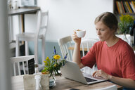 Young woman using laptop at table in a cafe - KNSF05325