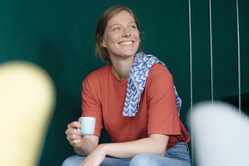 Smiling young woman sitting in a cafe holding espresso cup - KNSF05331