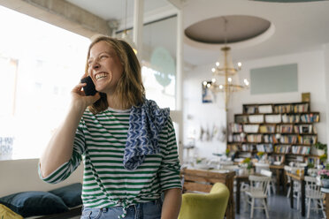 Laughing young woman on cell phone in a cafe - KNSF05352