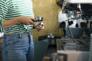 Close-up of young woman preparing coffee in a cafe - KNSF05355