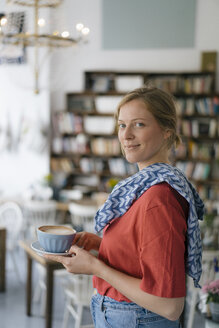 Portrait of smiling young woman serving coffee in a cafe - KNSF05358