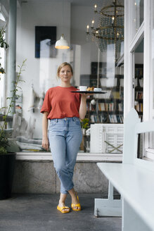 Portrait of young woman serving coffee and cake in a cafe - KNSF05364