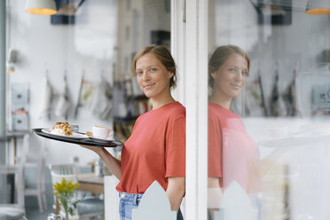 Portrait of smiling young woman serving coffee and cake in a cafe - KNSF05367