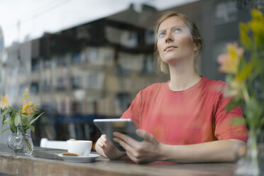 Young woman using tablet at the window in a cafe - KNSF05370