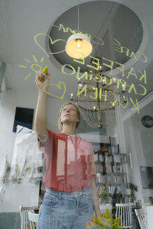 Young woman writing offer on windowpane in a cafe - KNSF05376