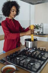 Woman standing in kitchen, preparing spaghetti - BOYF00958