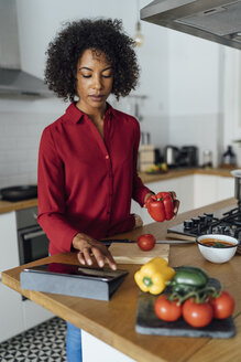 Woman standing in kitchen, chopping vegetables, using digital tablet - BOYF00961