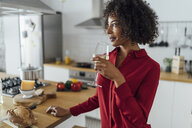 Woman standing in kitchen, drinking a glass of white wine - BOYF00985