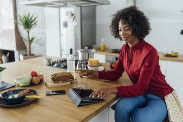 Woman sitting in kitchen with a glass of white wine, using digital tablet - BOYF00988