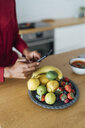 Woman taking pictures of fruits on a plate - BOYF00997