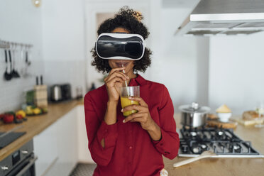 Woman standing in her kitchen, wearing VR goggles, drinking orange juice - BOYF01000