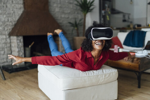 Woman lying on seating furniture, wearing VR goggles, pretending to fly - BOYF01006