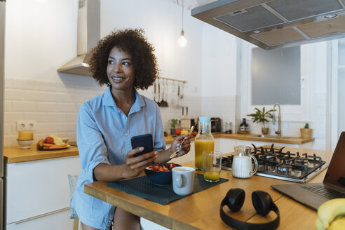 Woman having breakfast in her kitchen, using smartphone - BOYF01012