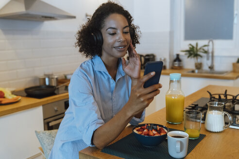 Woman with headphones, using smartphone in her kitchen - BOYF01015