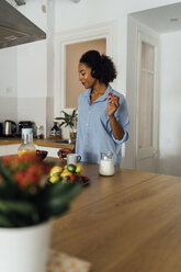 Woman having a healthy breakfast in her kitchen, listening music - BOYF01027