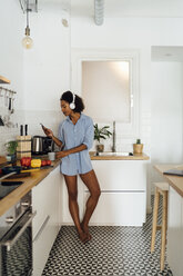 Woman with headphones, using smartphone and drinking coffee for breakfast in her kitchen - BOYF01030