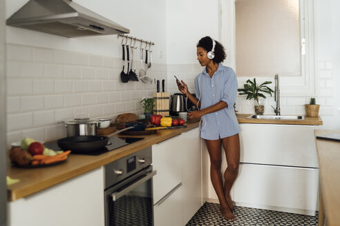 Woman with headphones, using smartphone and drinking coffee for breakfast in her kitchen - BOYF01033