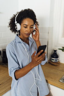 Woman with headphones, using smartphone in her kitchen - BOYF01036