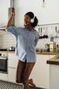 Woman dancing and listening music in the morning in her kitchen - BOYF01042