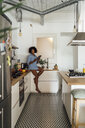 Woman sitting on worktop of her kitchen, using digital tablet in the morning - BOYF01048