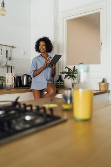 Woman sitting on worktop of her kitchen, using digital tablet in the morning - BOYF01051