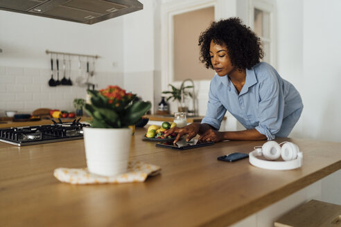 Woman using digital tablet and having a healthy breakfast in her kitchen - BOYF01054