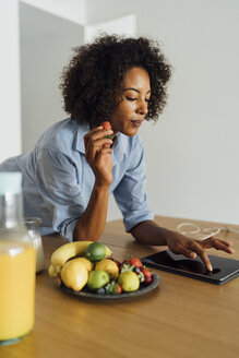 Woman using digital tablet and having a healthy breakfast in her kitchen - BOYF01057