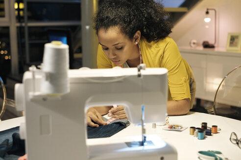 Female entrepreneur measuring jeans on table in office - CAVF54596