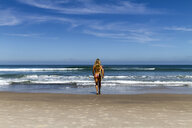 Rear view of woman in bikini carrying surfboard while walking towards sea against blue sky during sunny day - CAVF54611