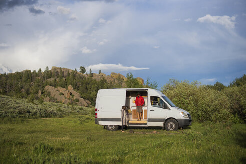 Man standing in motor home against cloudy sky at forest - CAVF54623