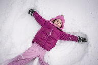 High angle portrait of happy girl making snow angel on field - CAVF54638