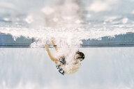 Full length of shirtless boy swimming underwater in pool - CAVF54662