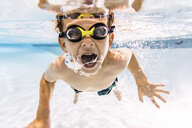 Portrait of shirtless boy with mouth open swimming in pool - CAVF54665