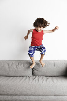 Happy boy jumping on sofa against wall at home - CAVF54686