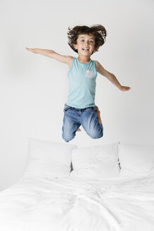 Portrait of happy boy with arms outstretched jumping on bed against wall at home - CAVF54692