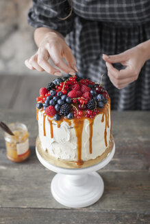 Midsection of woman icing cake with berry fruits on wooden table at home - CAVF54698