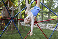 Portrait of cute happy girl hanging upside down on jungle gym against trees at playground - CAVF54704