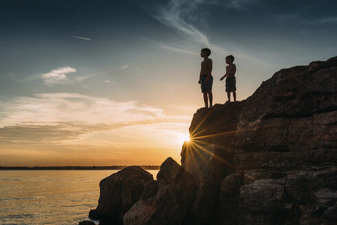 Low angle view of shirtless brothers standing on rocks by river against sky during sunset - CAVF54710