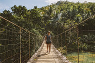 Woman walking on footbridge over river in forest - CAVF54755