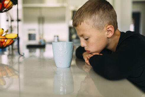 Side view of tired boy with tea cup resting head on kitchen counter at home - CAVF54779