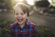 Cheerful boy looking away at park - CAVF54782