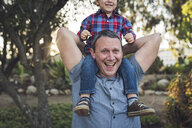 Portrait of cheerful father carrying son on shoulders while playing with him at park - CAVF54788